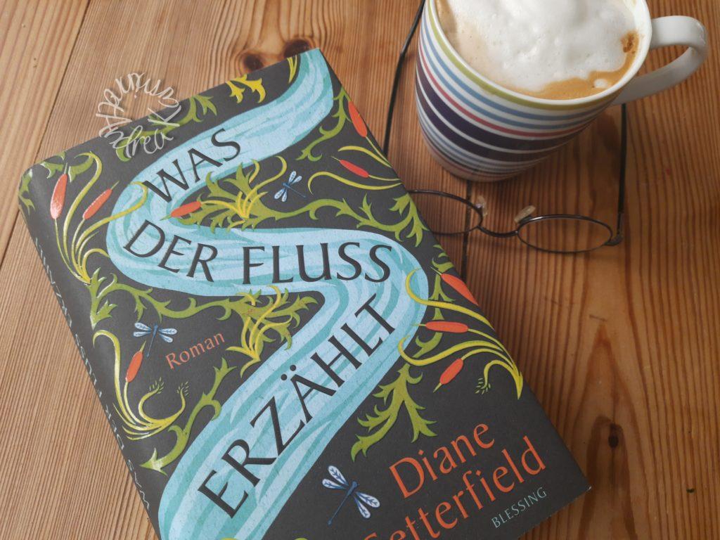 Das Buch Was der Fluss erzählt liegt auf einem Tisch daneben eine Brille und eine Tasse Kaffee